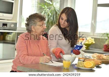 Homecare helping elderly woman doing crossword - stock photo