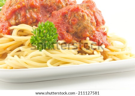 Homecooked hot spaghetti and meatballs with parsley garnish