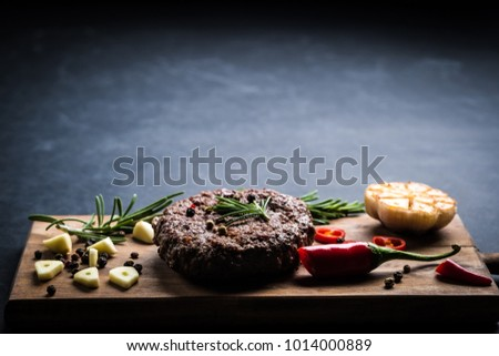 Homeemade beef burger cutlet with herbs and spices on wooden cooking board. Space for text