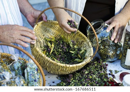 Homegrown dry herbs in the basket, jar and on the table  - stock photo