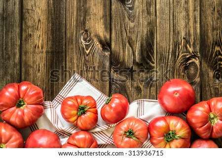 Homegrown tomatoes, fresh summer vegetables on rustic wood background with copy space, top view, close-up.