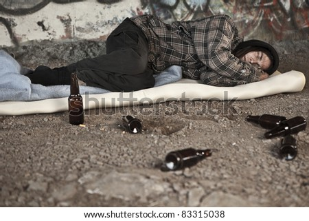 Homeless alcoholic sleeping outdoors - stock photo