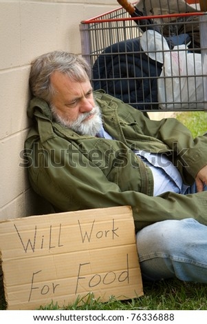 Homeless and hopeless man in an old army jacket waits for a handout. - stock photo