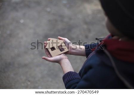 homeless boy holding a cardboard house, dirty hand - stock photo