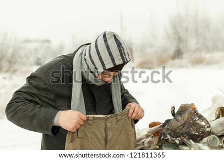 Homeless find trousers in the  dumpster - stock photo