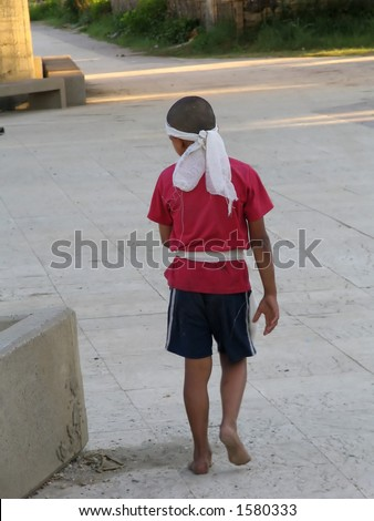 homeless gypsy boy walking barefooted and alone, looking for food, help and mercy - stock photo