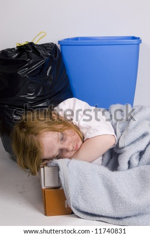 homeless kid sleeping in a box surrounded by trash - stock photo