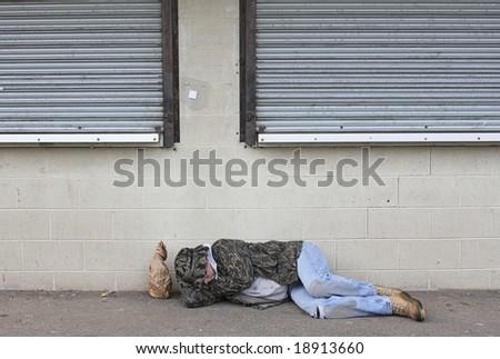 Homeless man asleep on the sidewalk - stock photo