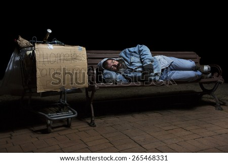 Homeless man at night sleeping on a park bench with his shopping cart full of his possessions - stock photo