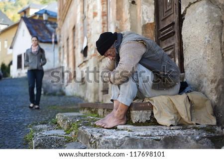 Homeless man begging on the street - stock photo
