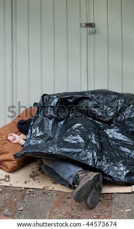 Homeless man curled up on the street under a plastic tarp. - stock photo