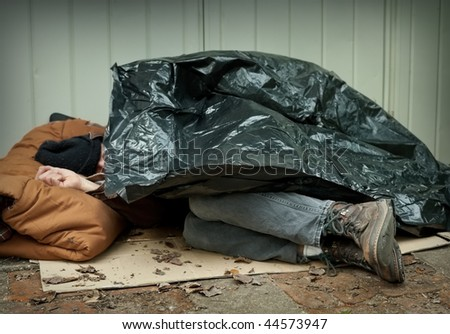 Homeless man curled up under a plastic tarpaulin, asleep on the street. - stock photo