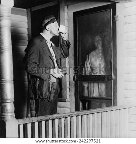 Homeless man in ragged clothes eating a meal standing as his benefactor keeps her distance behind her front door. 1919 photo by N.D. Hillis. - stock photo