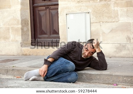 homeless man lying in city street near house door - stock photo