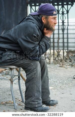 Homeless man on the sidewalk. - stock photo