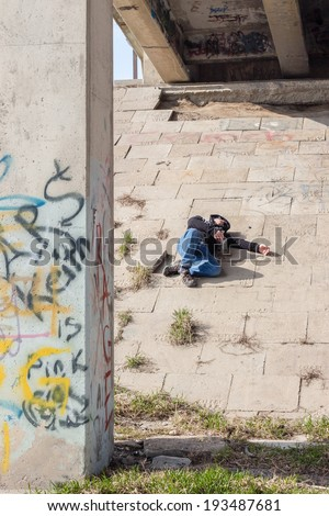 homeless man passed out and sleeping under the bridge on a cement pad on a warm spring day.  - stock photo