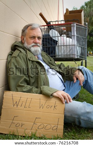 Homeless man rests leaning against a wall hold a sign with his possessions in a grocery cart. - stock photo
