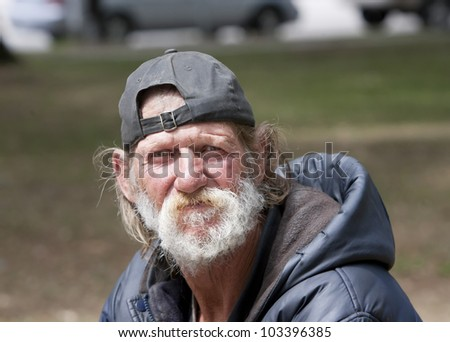 Homeless man sitting outdoors during the day - stock photo