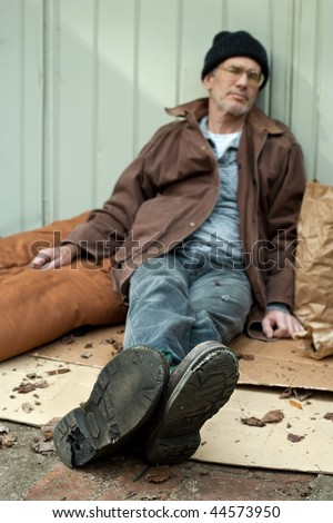 Homeless man sleeping on the streets, seated position, surrounded by his bags, etc. Selective focus with boot soles full of holes in focus, and the man's face blurry. - stock photo
