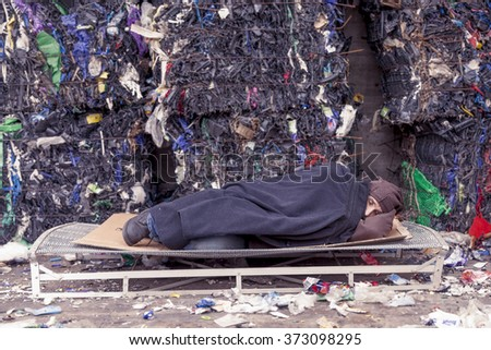 homeless man sleeps in the waste on a wire mesh of bed - stock photo