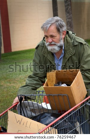 Homeless man wearing an old army coat pushes a shopping cart holding his possessions. - stock photo