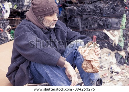 homeless man with a bottle of red wine in landfill - stock photo