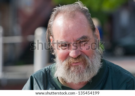 Homeless man with a smile on his face. Outdoors during the daytime. - stock photo