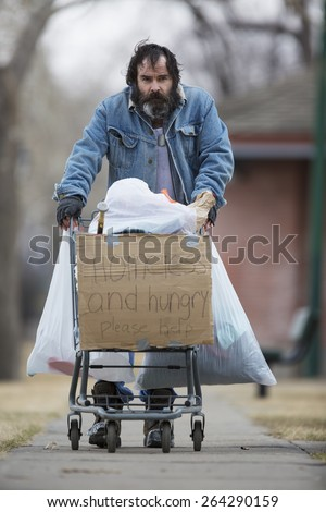 Homeless man with beard pushing a shopping cart with all his possessions. - stock photo