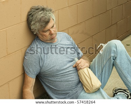 homeless man with his bottle passed out in an alley - stock photo