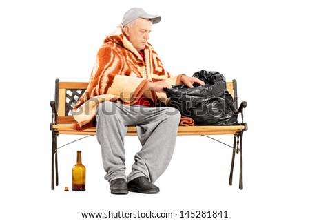 Homeless mature man sitting on a bench and looking for something in his bag, isolated on white background - stock photo