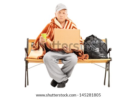 Homeless mature man sitting on a bench, his worldly possessions next to him, holding a blank cardboard isolated on white background