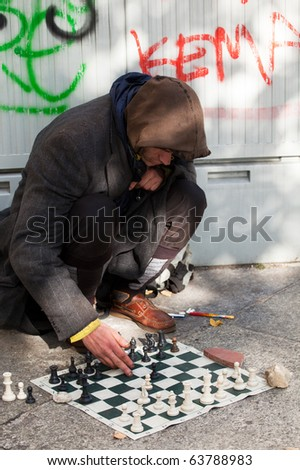 Homeless Men chess player siting on the floor - stock photo