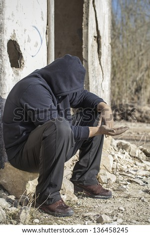 Homeless person begging near the destroyed  house