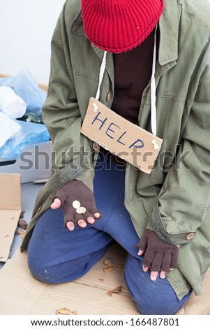 Homeless person in need holding only a few cents in his hand - stock photo