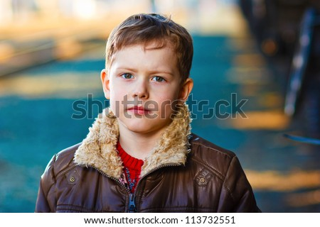 homeless sad blond abandoned alone child is boy on street in jacket - stock photo