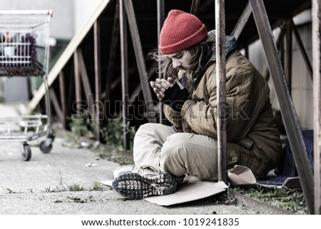 Homeless, sad man in a beanie sitting outside and feeling cold, trying to warm up his hands