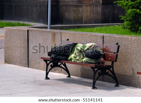 Homeless sleeping on bench during the day. - stock photo