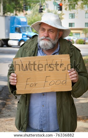 "Homeless veteran begging at the side of the road holding a sign that says, ""Will Work For Food."" - stock photo"