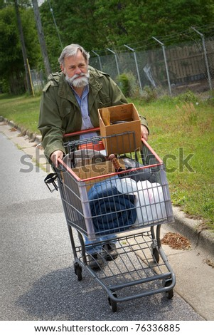 Homeless Vietnam veteran pushes a shopping cart containing his possessions down the side of the street. - stock photo