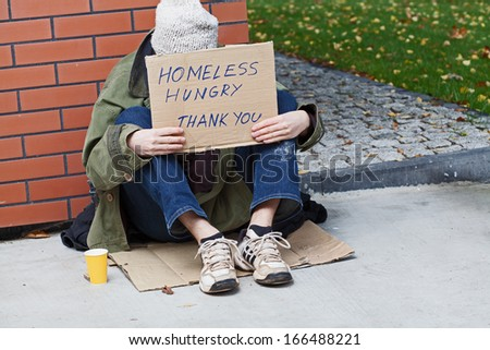 Homeless with cardboard on his neck drinking hot tea - stock photo