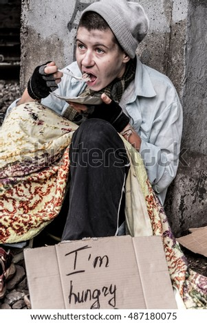 Homeless woman sitting near the rail track having meal