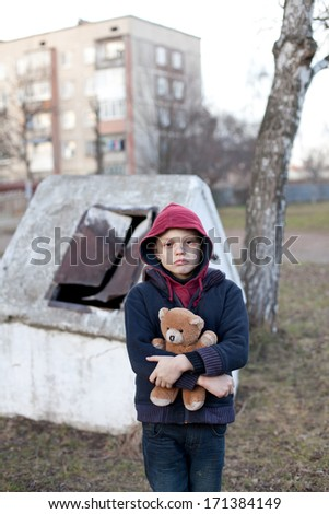 homeless young boy with bear