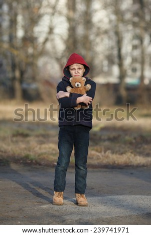 homeless young boy with bear - stock photo