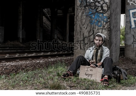 Homeless young woman sitting under the bridge with sign asking for food