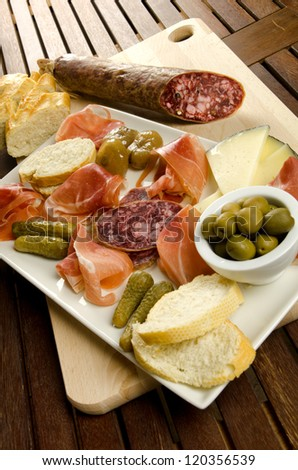 Homelike appetizer with salami, bread, olives, cheese, ham, pickles and red wine - stock photo