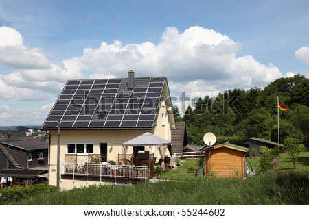 Homely house with solar panels on the roof - stock photo