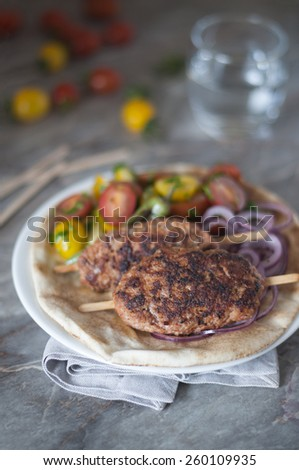 Homemade adana kebab with traditional salads