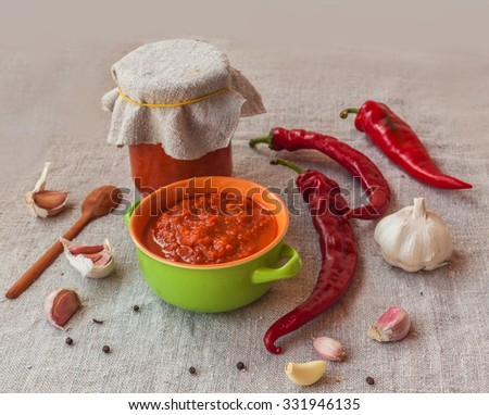 Homemade adjika in a glass jar next to the hot pepper and garlic on canvas - stock photo