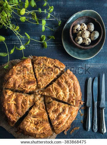 Homemade and sliced double cheese pie and Quail eggs on wooden background,Easter cuisine  - stock photo