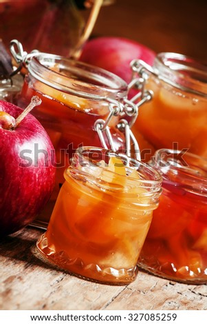 Homemade apple jam in banks in the autumn background with ripe apples and red leaves on the old wooden table, selective focus - stock photo